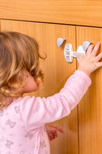 A child lock prevents a toddler from opening a cabinet.