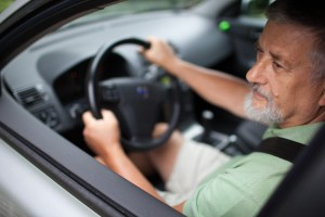 An older man drives cautiously while wearing his seat belt.