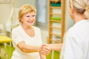 A female naturopathic doctor welcomes an older female patient with a handshake.