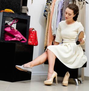 A woman decides between a high heeled shoe and a loafer.