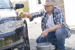 A man washes his car with a sponge and bucket.
