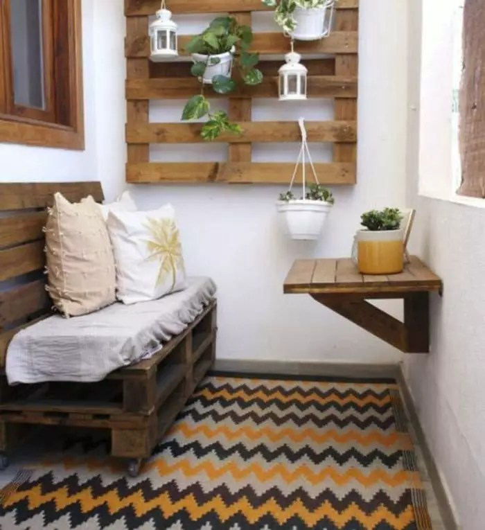 a room furnished just with pallets: a sofa made with pallets, a shelf made with pallets and a small table
