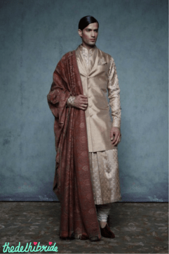 A gold brocade sleeveless sherwani, with pleated neckline, worn with a long, pleated silk brocade kurta and churidar. Look adorned with traditional Jamewar shawl and velvet juttis.
