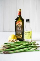 The ingredients for this salad - olive oil, vinegar, asparagus, pistachios, lemon juice