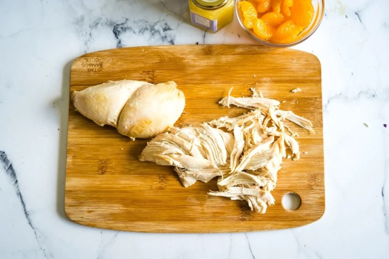 Shredded chicken best ready to be put in a salad on a bamboo cutting board