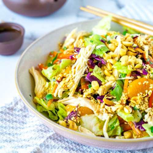 A big bowl of Chinese Chicken Salad on a white and grey napkin with chopsticks
