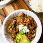 Overhead shot of a bowl of chili on a wood table garnished with avocado, sour cream with some shredded cheese nearby