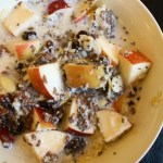 A mixture of apples, flax seeds, hemp hearts, chia seeds, shredded coconut and walnuts warmed up with some almond milk in a bowl on a black background