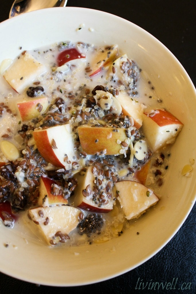 A bowl of apple slices, seeds, nuts and coconut warmed up with almond milk in a cream coloured bowl