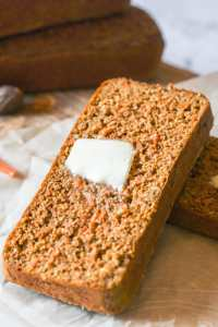Close up of a carrot cake breakfast bread with a dollop of melting butter on a white background