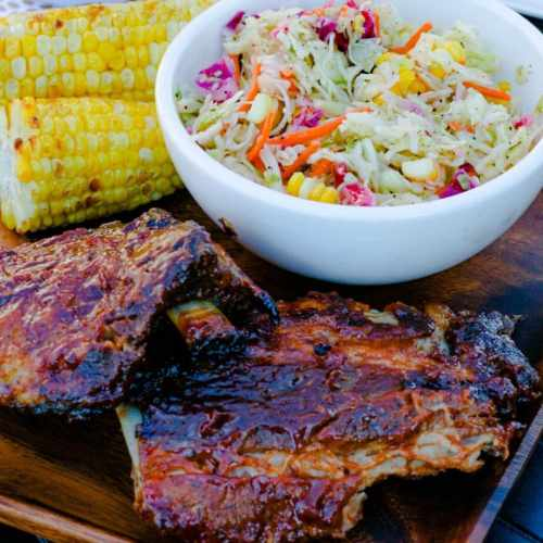 Baby back ribs painted with rich barbecue sauce with a side of fire roasted corn on the cob and coleslaw