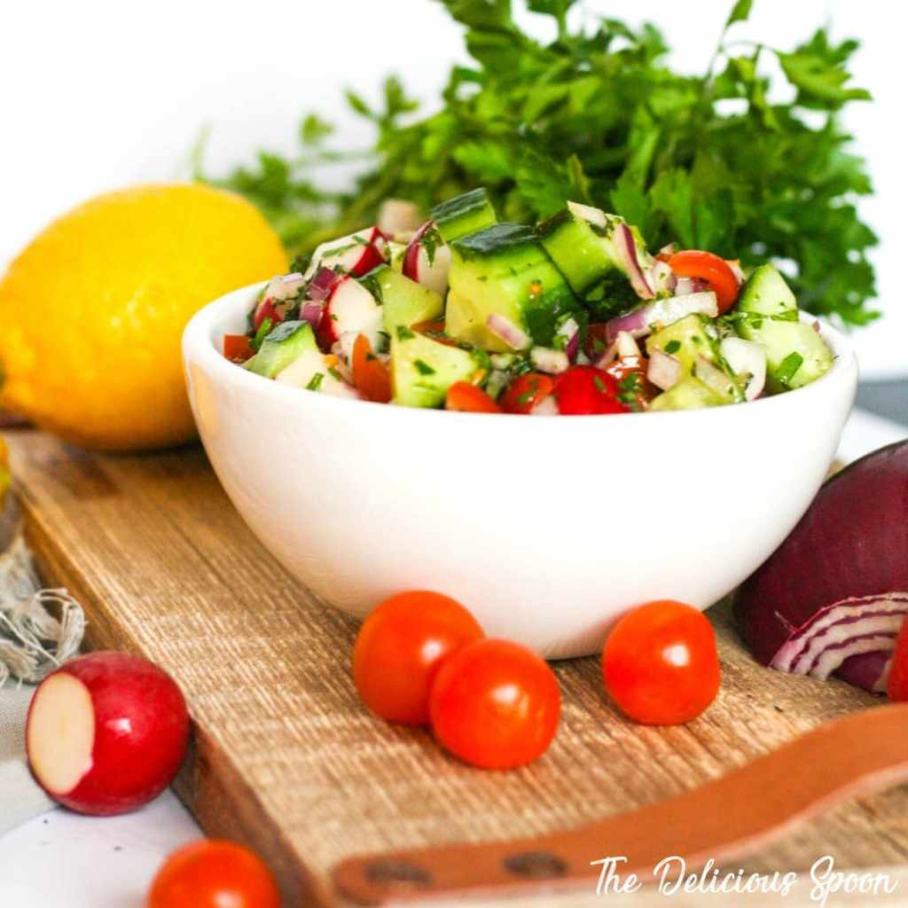 A bowl of Fattoush Salad displayed on a rustic wood cutting board surrounded by fresh vegetables like radishes, cucumber, lemon and tomatoes