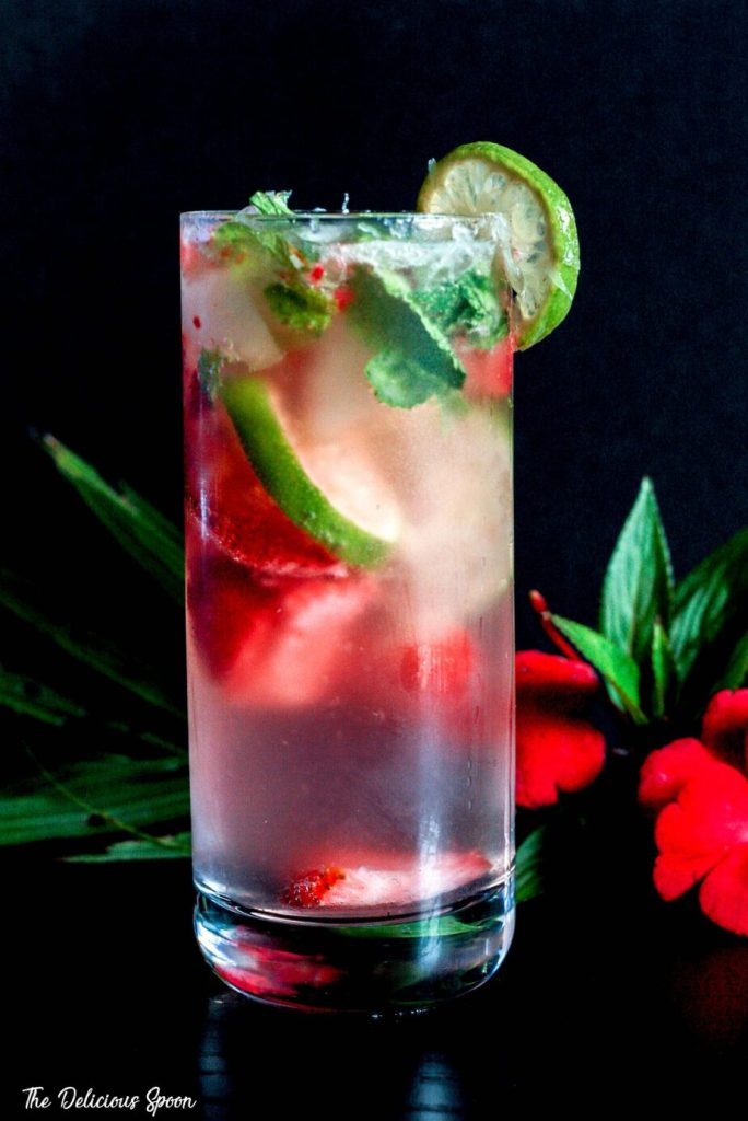 Strawberry Mojito in a highball glass garnished with a lemon wedge on a black background surrounded by tropical flowers