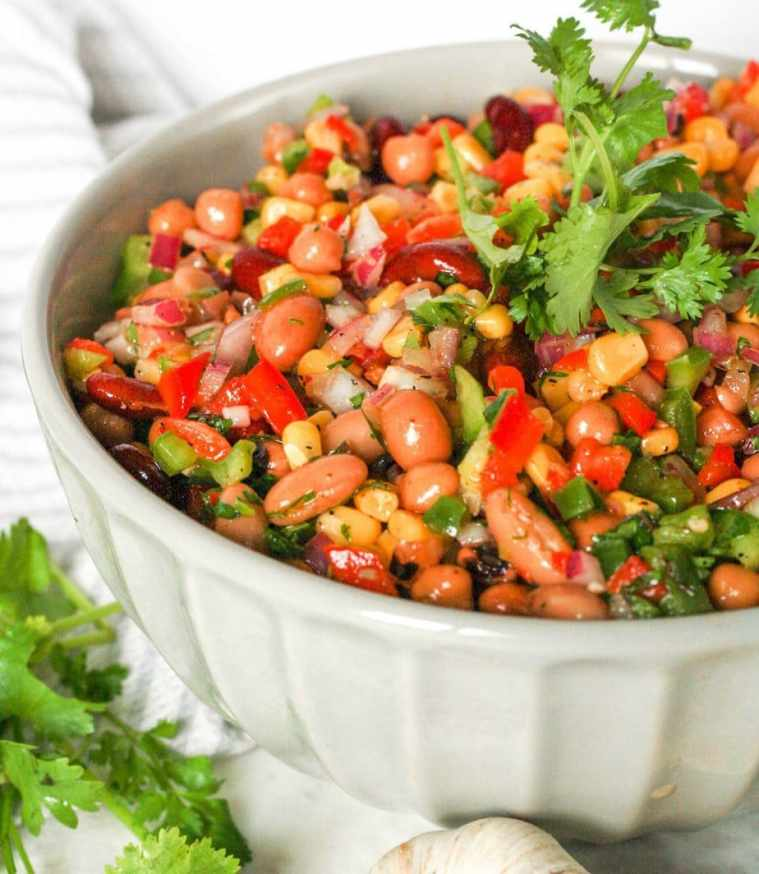 Close up of a bowl of Mexican Bean Salad topped with a sprig of fresh cilatnro