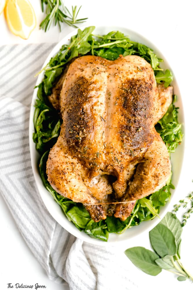 Whole Roasted Chicken with Dijon Herb Butter in a white serving bowl