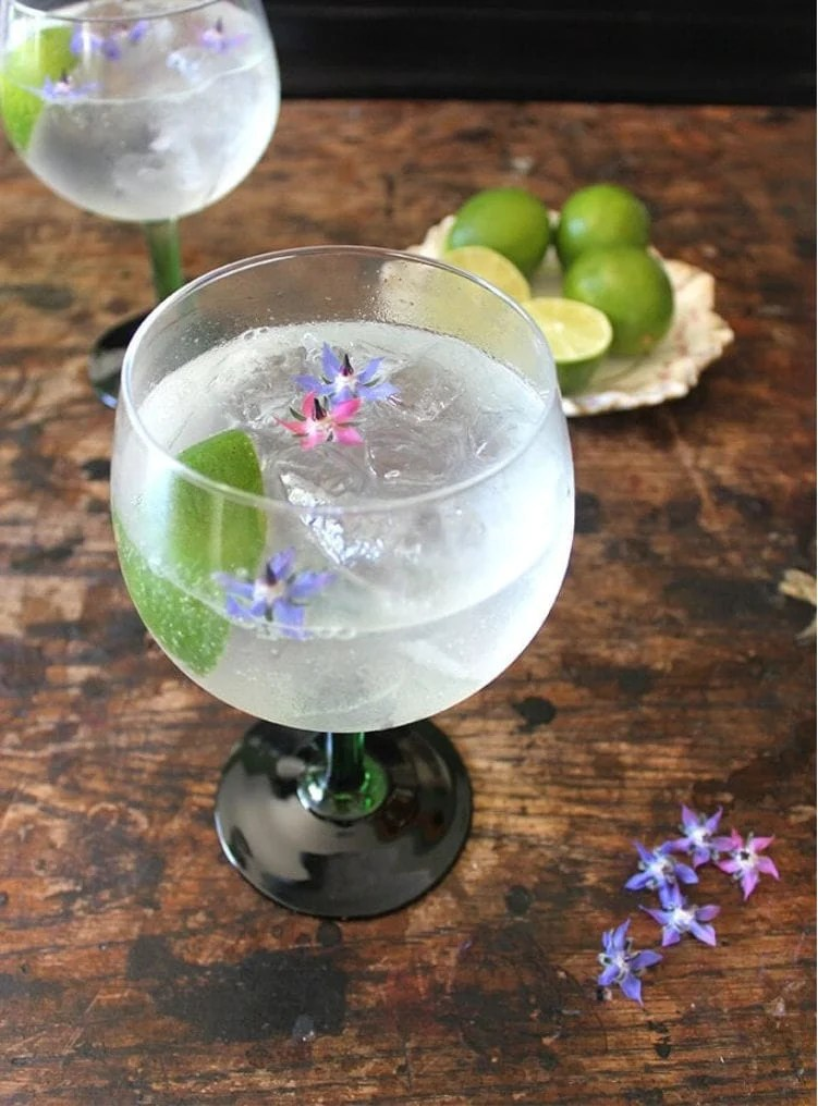 Gin Rickey Cocktail on a wood table decorated with small purple flowers