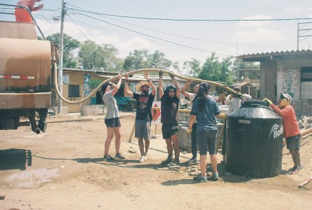 Students filling stationary water tanks on-site to use for cement mixing.