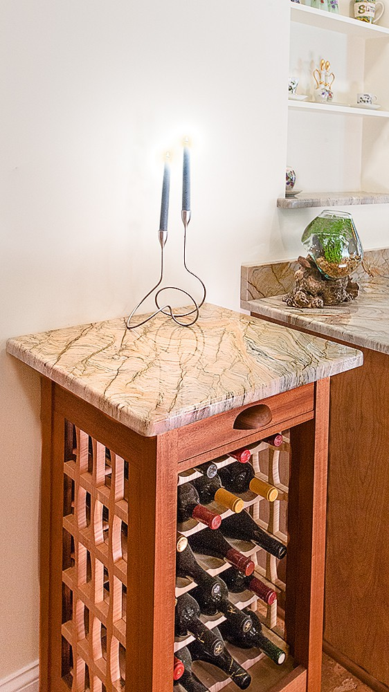 This wine storage rack showcases a quartzite top that matches the kitchen counters. Natural stone has many uses as design features including fireplace surrounds, bar tops, desk tops, fireplace surrounds. Photo credit: Ripano Stoneworks.