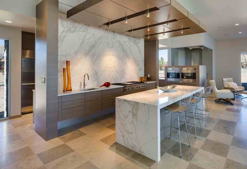 Calacatta Gold marble creates a wraparound kitchen island top and oversized backsplash in this contemporary kitchen. Photo credit: Rocky Mountain Stone.