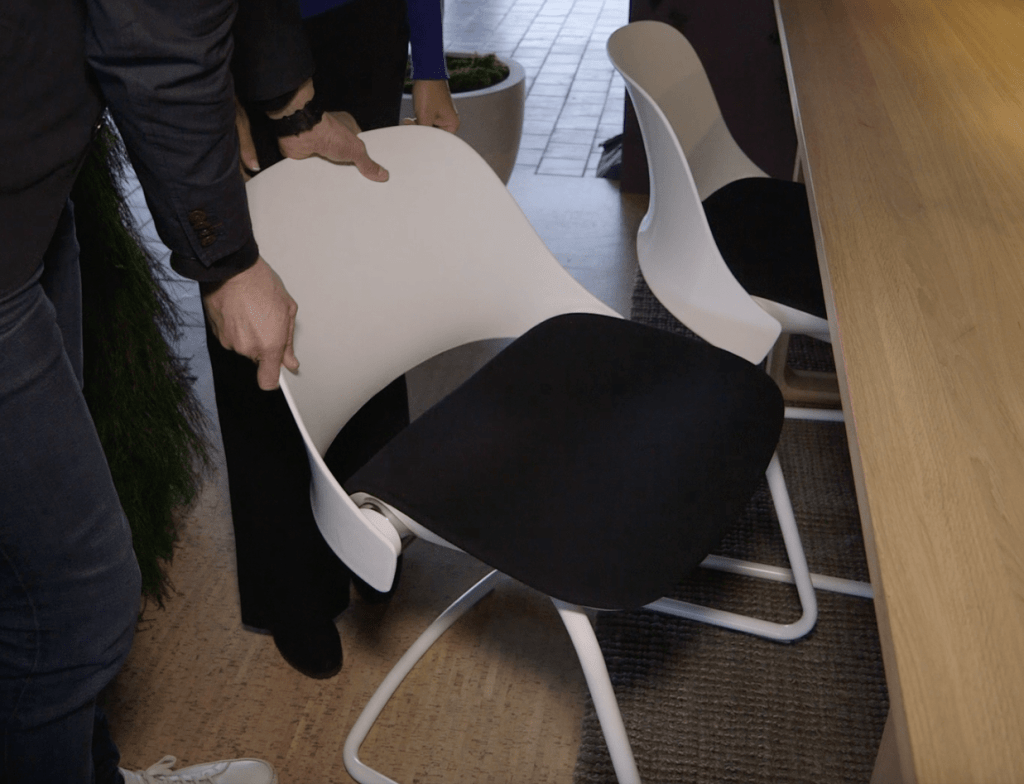 Designer Todd Bracher demonstrates how the Trea chair back reclines when you sit in it and adjusts to any size person seated in it. Photo Credit: The Design Tourist
