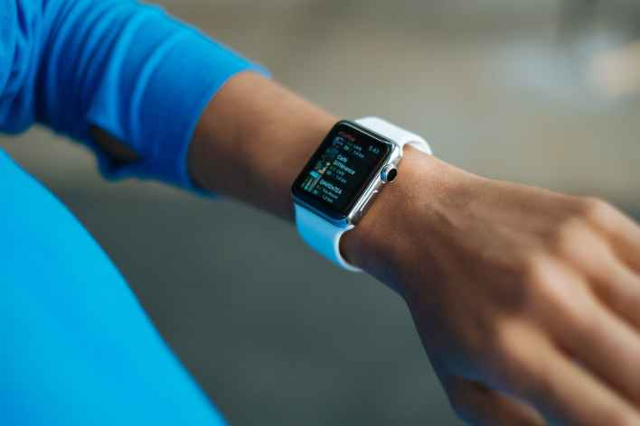 person wearing white silicone strap black smart watch