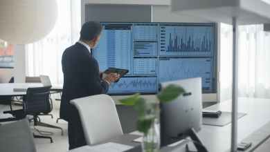 man looking at a screen with stock market data