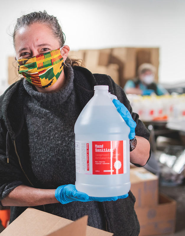 Person holding a gallon of hand sanitizer