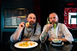 Speakeasy bartender Bryan Burns and DBA Chef Ernest Cornelius enjoy dinner for two before guests arrive (left to right)