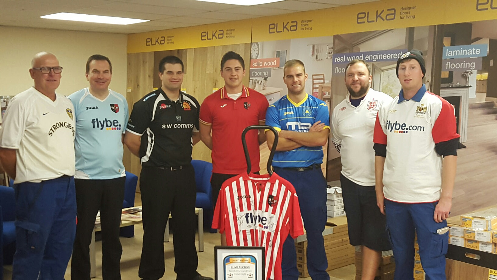 staff from RGB Exeter in their favourite team's shirt