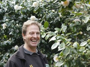 Senior Gardener Colin Clark and prize-winning camellia Mrs D W Davis.