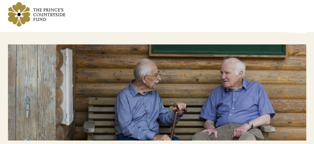 two men on a bench talking to each other and a Prince's Countryside Fund logo