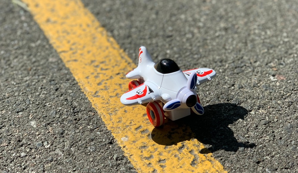 a toy plane on a road with a yellow line