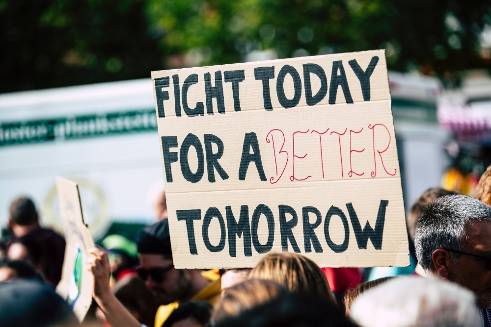 a protest with a banner saying ' fight today for a better tomorrow'