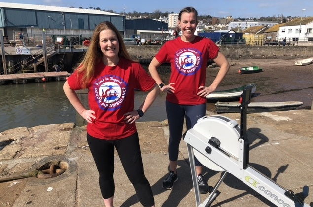 two women in red t-shirts next to a rowing machine