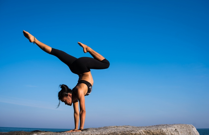 woman doing yoga on a cliff