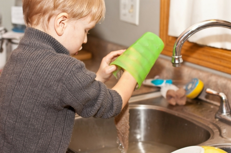 Young boy doing dishes to help out around the house.
