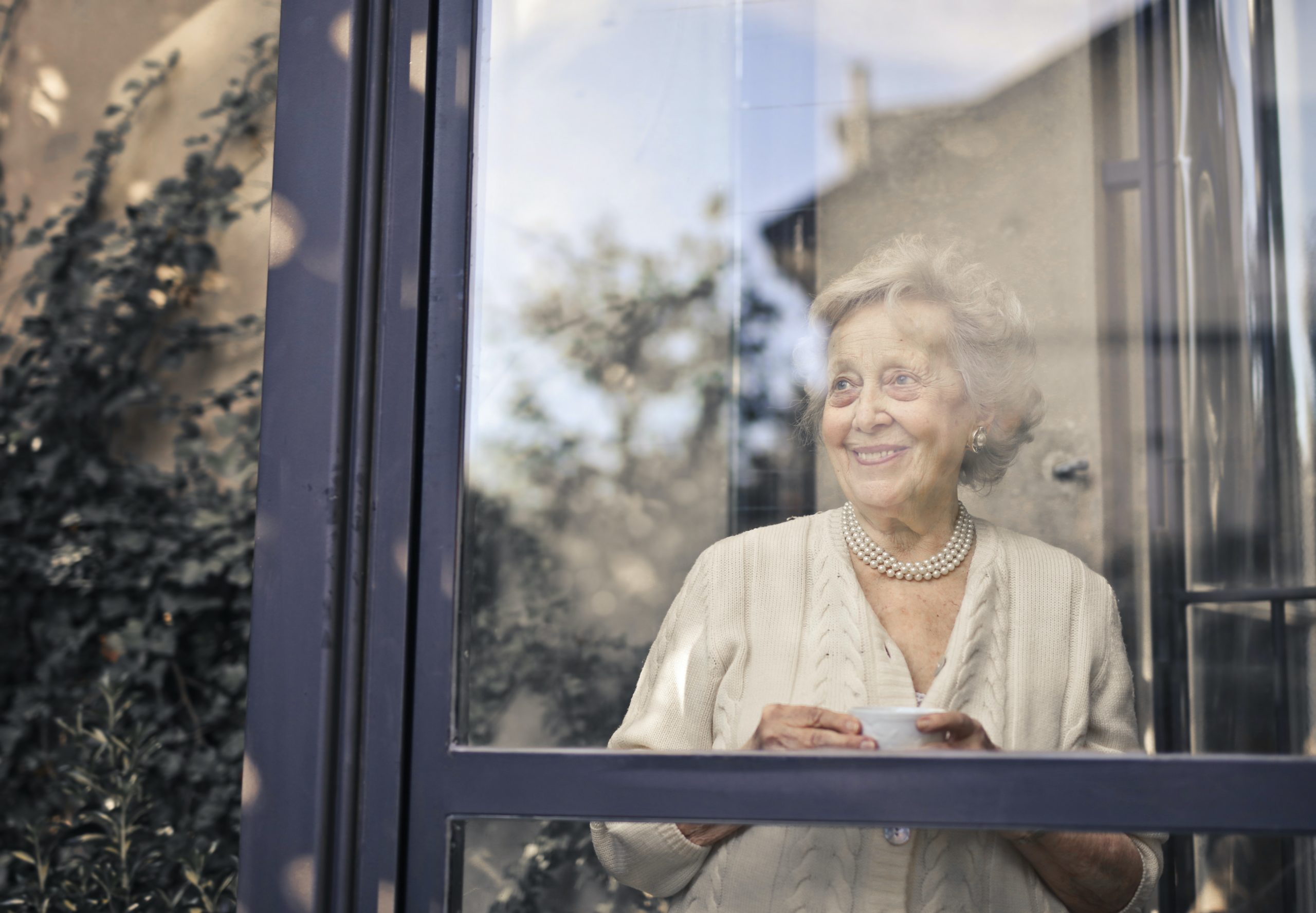 elderly woman looking out a large window