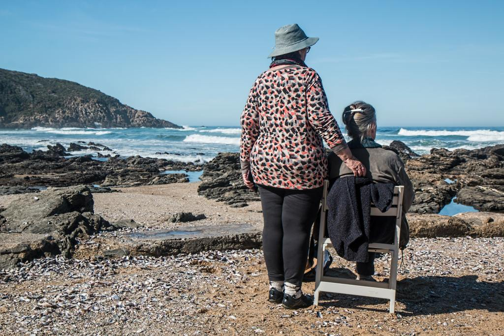 Two Senior females staring out at the ocean one sitting and one standing.