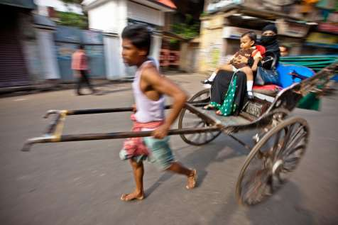 Families rely on the cheap transportation the pulled rickshaw provides in downtown Kolkata.