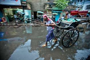 The rain stops, yet the puddles and the work continues. This man plies the streets looking for a fair. An empty rickshaw does not pay the bills.