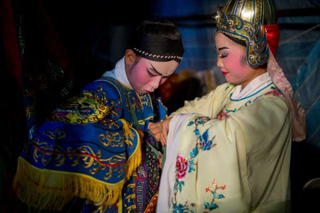 Costuming can be quite intricate and ornate. Performers help each other Into their costumes