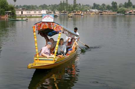 A shikara on Dal Lake drops of tourist on the Bulavard.