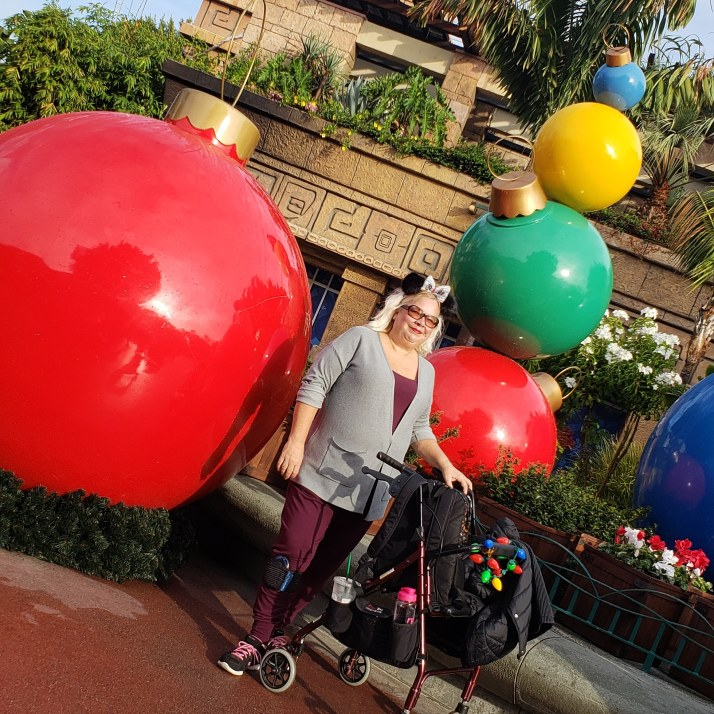 The Disabled Diva at Disneyland during the 2018 holiday season using a rollator to rest her back and legs as needed. This is one example of how she makes pain management modifications during the holiday season.