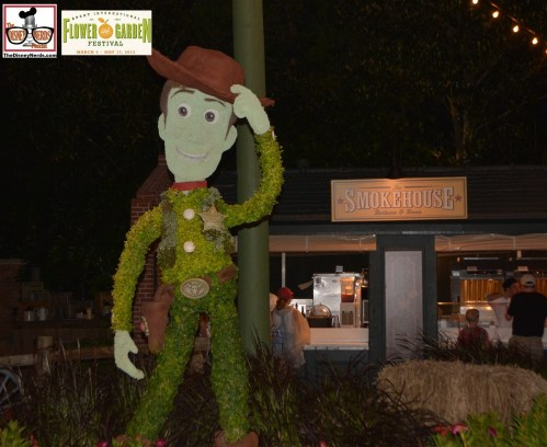"Woody welcomes all to the Smokehouse outdoor kitchen featuring Pulled Pork Sliders; Beef Brisket Burnt Ends Has' smoked Debreziner Sausage and ""Pigglylicious Bacon Cupcakes"" - Epcot International Flower and Garden Festival 2015"
