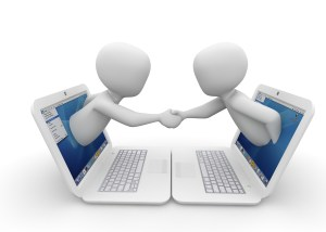 Two cartoon characters shaking hands in agreement as they emerge from laptop screens