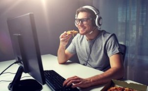 gamer with headphones eating pizza in front of computer screen