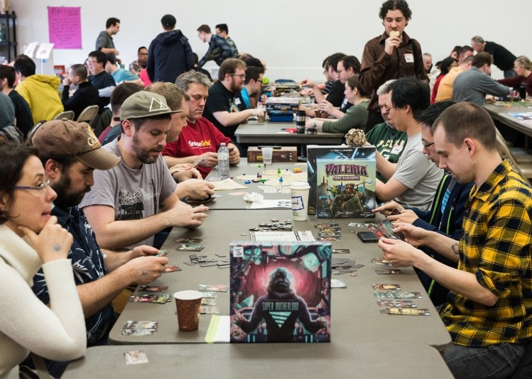 People at a convention playing various tabletop roleplaying game systems