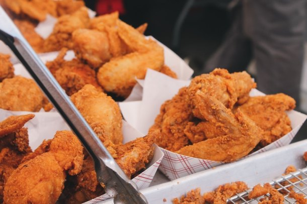a bunch of fried chicken wings in paper baskets