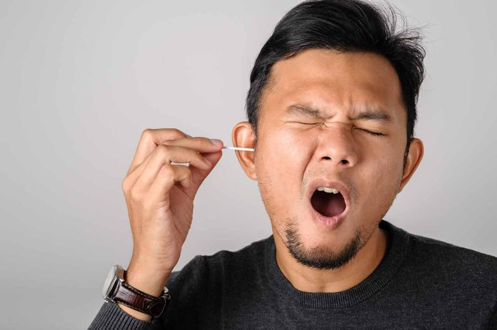 Man cleaning ears with pick