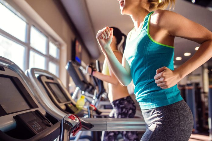 Two attractive fit women running in sports clothes on treadmills in modern gym 2048 x 1363